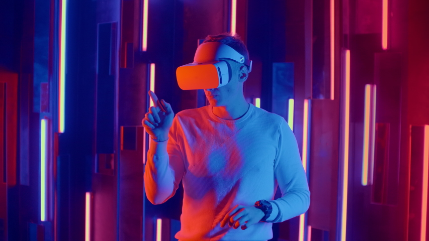 Faceless man wearing VR headset in dark space with neon light lamps, user turning head side to side looking virtual reality, shooting through colored flares and bokeh on foreground.   Shutterstock HD Video #1045442545