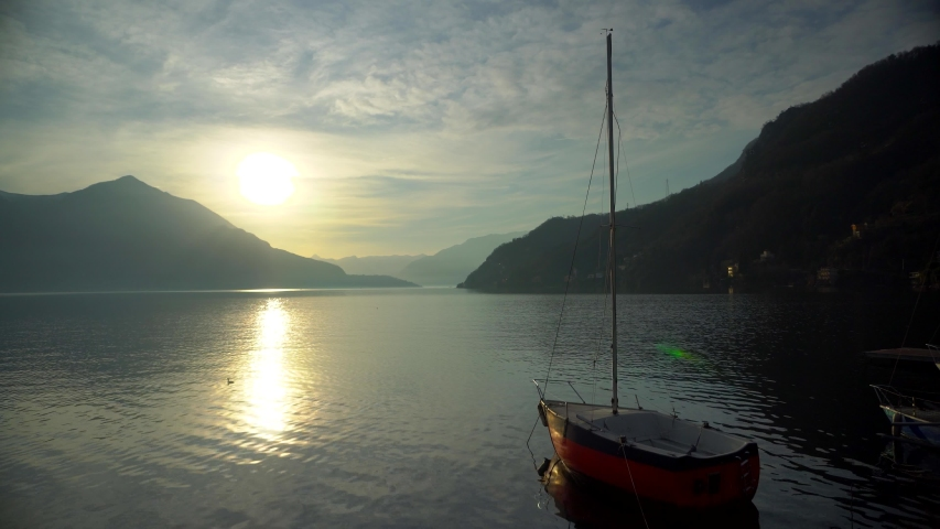 Sailing yacht moored off the coast on Lake Como in Italy before sunset over the mountain horizon of alpine peaks. Cinematic frame. Romantic atmosphere. Calm and pacifying scene. Sailboat | Shutterstock HD Video #1046020255