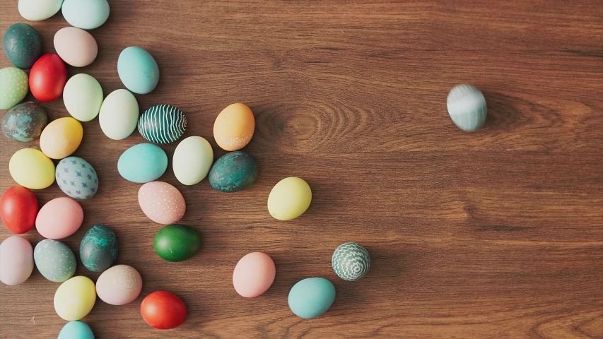 Colorful Easter eggs rolling on wooden table. Easter holiday decorations, Easter concept background.  | Shutterstock HD Video #1046105455