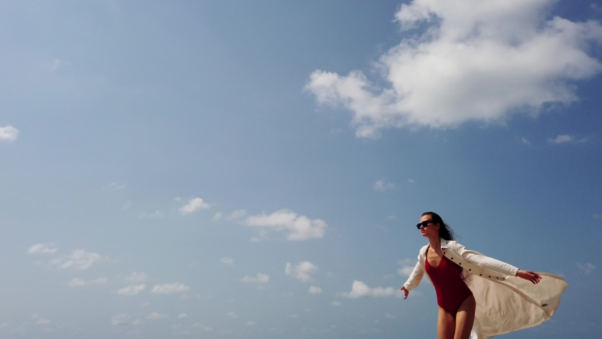 Young lady in red swim suit, long white dress and sun glasses runs on beach on background of blue sky with clouds. View from below. Positive. Dress fluttering on wind. Honeymoon. Super slow motion.    Shutterstock HD Video #1046806585