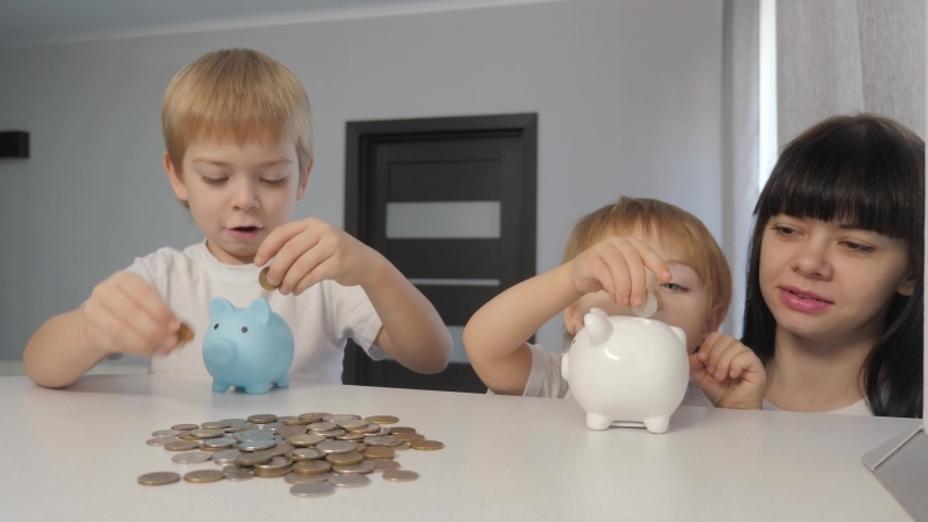 Happy family saving money concept. mom and children put money in a piggy bank. little girl and boy put coins in a piggy lifestyle bank | Shutterstock HD Video #1046814925