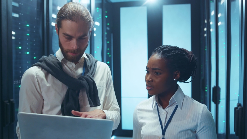 Couple of IT admins laughing together inside working server cabinet. Stressed man makes a mistake and negatively surprises his colleague.   Shutterstock HD Video #1046828425