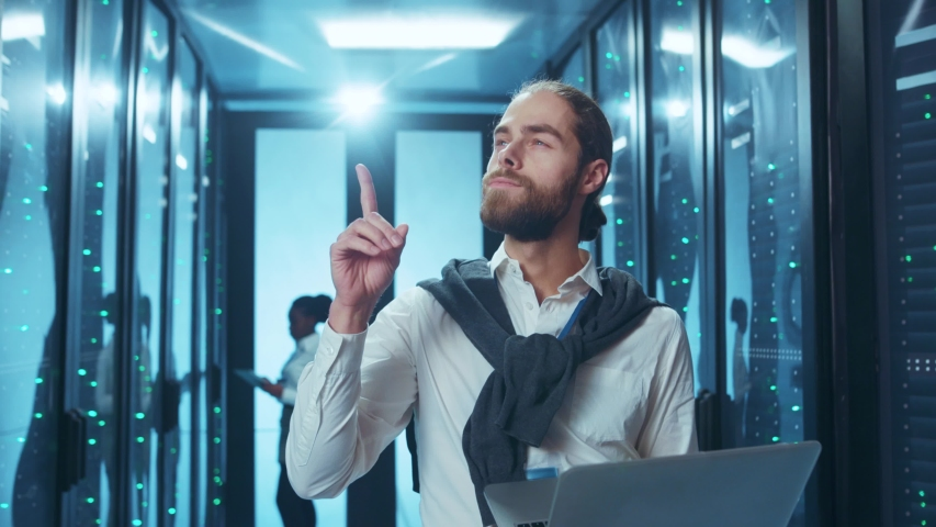 Bearded datacenter IT technician working on laptop in server room coming up with solution to a problem. People and technology.   Shutterstock HD Video #1046828455