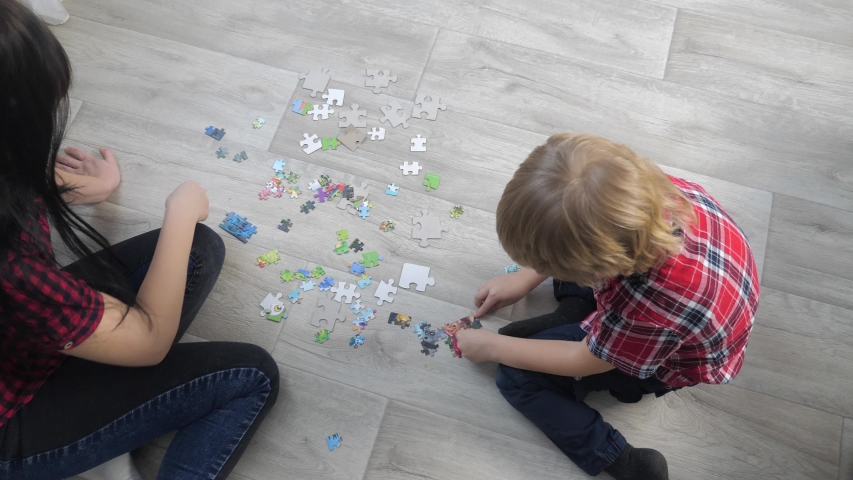 Happy family lifestyle collection puzzles teamwork. development of fine motor skills and thinking. little son boy a and girl mom collect mosaic puzzles | Shutterstock HD Video #1046885665