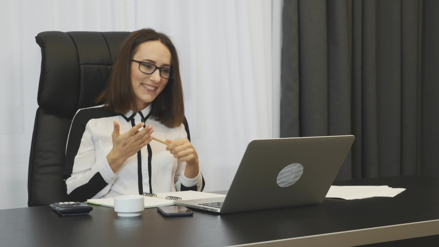 Happy business woman celebrating good news seen on laptop. Successful young woman excited with financial results on trading stock market. Trader won money on stocks. Smiling female showing yes sign | Shutterstock HD Video #1046891755