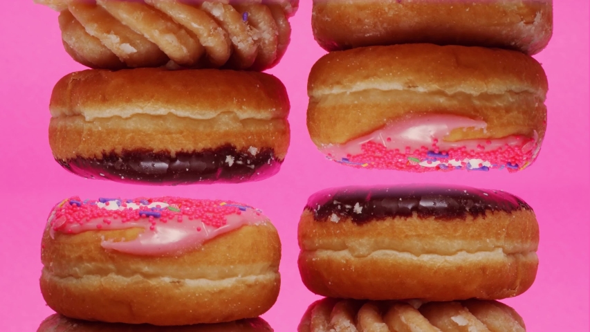 Donuts piles rotating from above and below. Stop motion animation with a bright pink background. Pop art concept.   Shutterstock HD Video #1046902735
