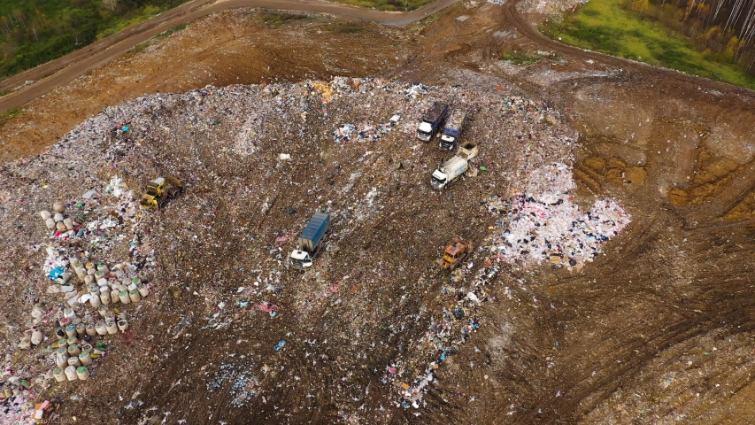 A pile of household trash with soil. Garbage landfill, top view. Problems with household waste. Garbage trucks unload garbage. | Shutterstock HD Video #1046904355