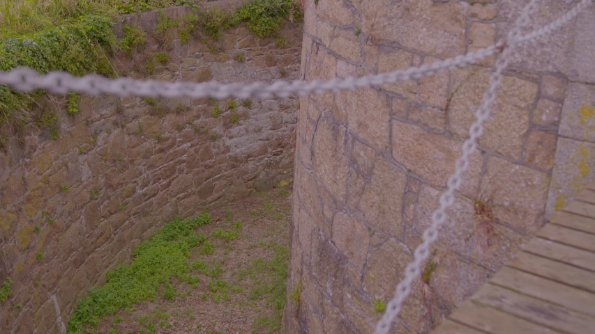 Close up showing a dry moat surrounding the circular Victoria Tower, with wooden drawbridge and chains | Shutterstock HD Video #1046929975