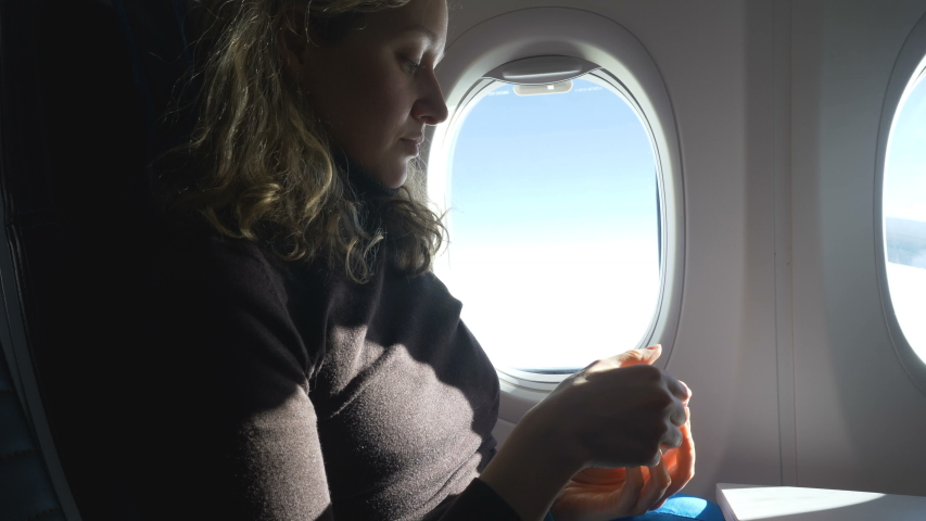 Hungry curly haired woman sits near porthole unpacks delicious cake and eats travelling by airliner closeup slow motion | Shutterstock HD Video #1046964595