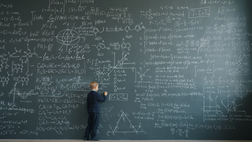 Prodigy child in suit is writing formulas on huge blackboard in school classroom concentrated on educational activity. Education and childhood concept. | Shutterstock HD Video #1046970145