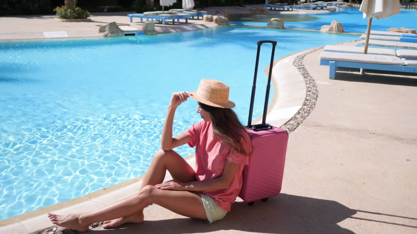 Young woman with pink case sits near swimming pool in hotel. Travel vacation concept. HD video in ProRes 1920x1080 | Shutterstock HD Video #1046972545