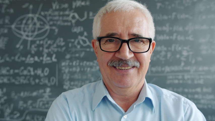 Portrait of happy mature man in glasses looking at camera smiling near chalkboard with formulas written with chalk. Education and positive emotions concept. | Shutterstock HD Video #1046977105