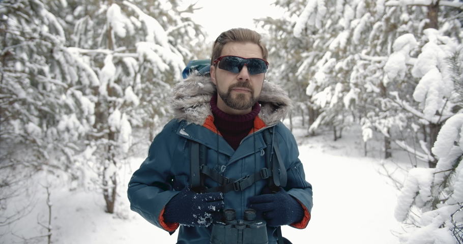 Front view of male enthusiast with trendy haircut wearing winter jacket, gloves and mirrored glasses walking in coniferous forest. Mature traveler with big backpack hiking outdoors. | Shutterstock HD Video #1047009355