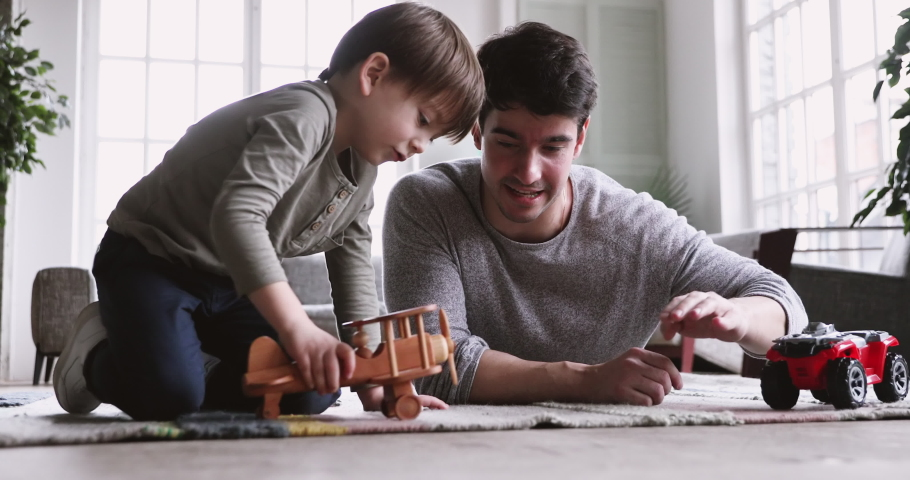 Young father and cute small kid son playing funny racing game relax on carpet floor at home. Happy male family adult dad and little child boy having fun with toy car plane engaged in leisure activity | Shutterstock HD Video #1047051055