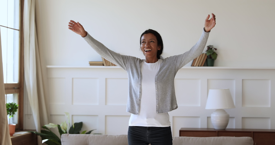 Overjoyed young african woman feeling joyful, thanking god for good luck. Thankful mixed race girl enjoying freedom alone at home. Excited homeowner spinning with stretched arms, real estate concept. | Shutterstock HD Video #1047056845