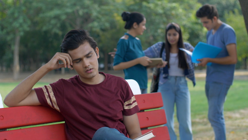 Unhappy Indian guy is very disappointed by his exam results - education failure. A young college student is sad and depressed after failing the examination while his classmates are celebrating succ... | Shutterstock HD Video #1047111805