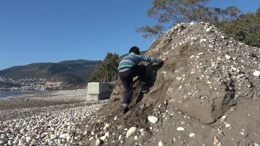 Finike, Turkey - 4th of January 2019: 4K Child fails to climb on a heap of sand and stones  | Shutterstock HD Video #1047182365