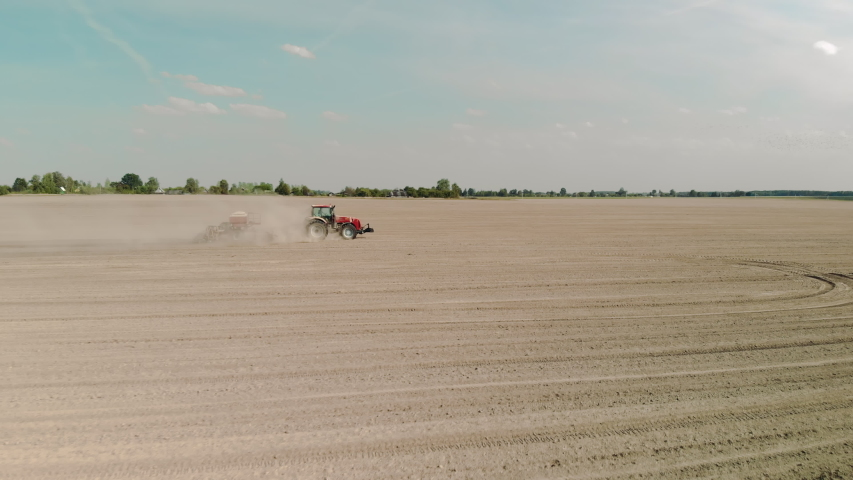 Aerial: moving the camera forward to a tractor with a tillage unit sowing in arid, dusty soil in Sunny weather. Agribusiness concept in the zone of risky agriculture | Shutterstock HD Video #1047187195