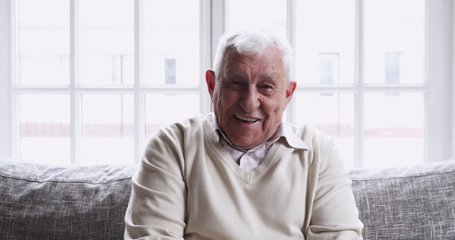 Happy senior 80s grandfather look talk to camera at home video calling recording vlog, smiling elderly adult man sit on sofa communicate in online chat, webcam view, old people making videocall