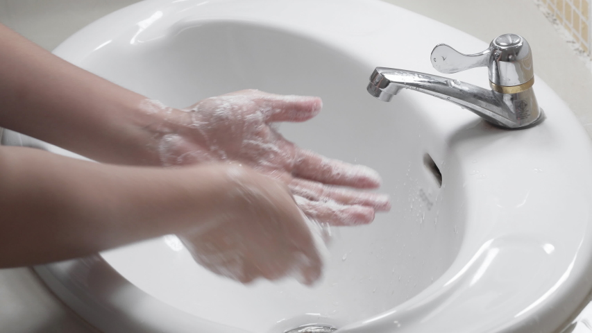 Close up of female lathering hands with soap before washing   | Shutterstock HD Video #1047983275