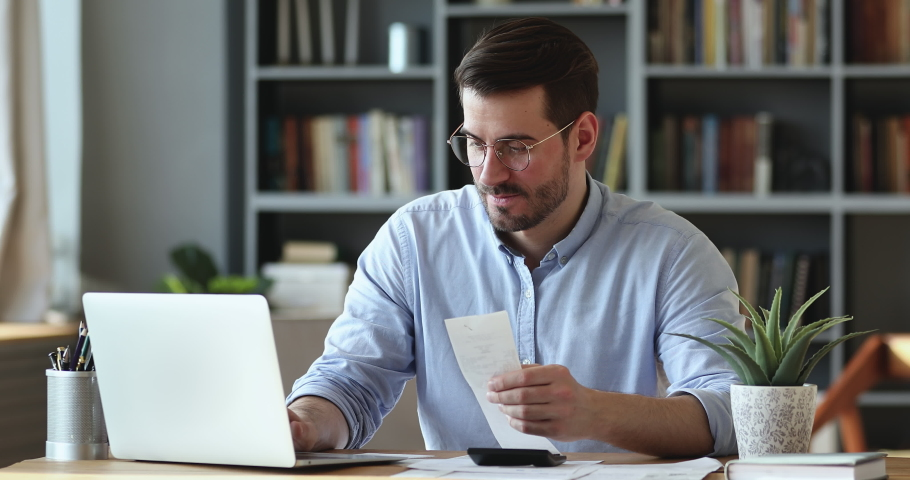 Focused businessman accountant doing calculation for online financial report at workplace. Serious man using calculator paying bill online holding paper sitting at home office desk. Accounting concept   Shutterstock HD Video #1048491175