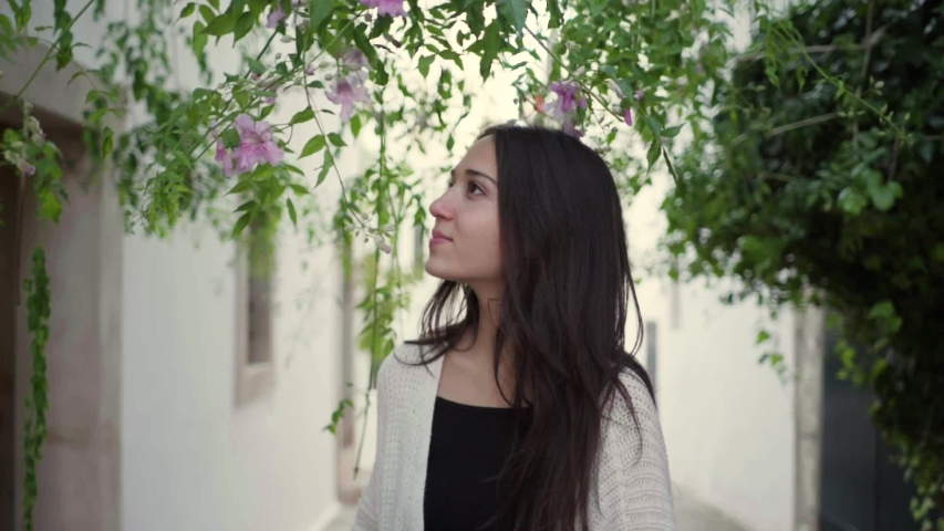 Young woman covering her eye with a pink flower | Shutterstock HD Video #1048610245