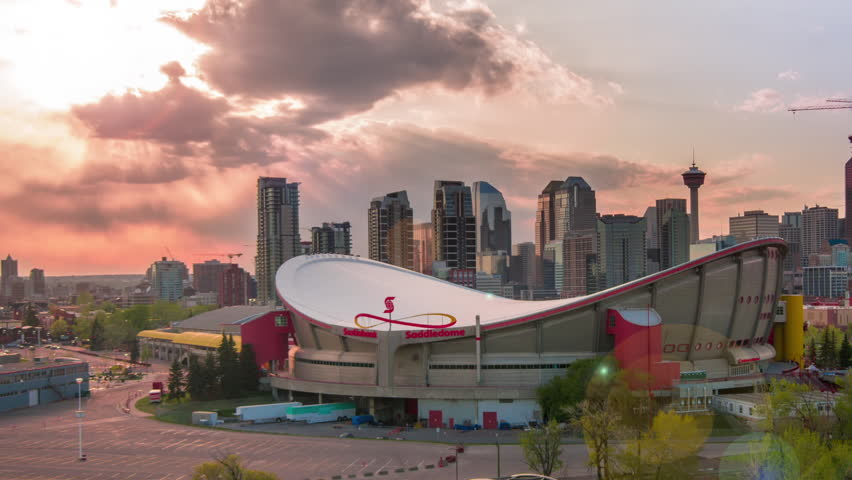 CALGARY, CANADA - MAY 9, 2015: Sunset Timelapse (static crop) of Scotiabank Saddledome with Calgary downtown skyline, and new foot bridge over Elbow River replaces 2013 flood washed out bridge.