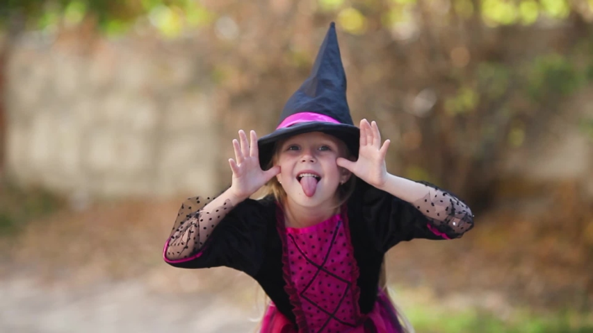 A girl in a witch costume is grimacing. Halloween holiday, October 31 | Shutterstock HD Video #1049510995