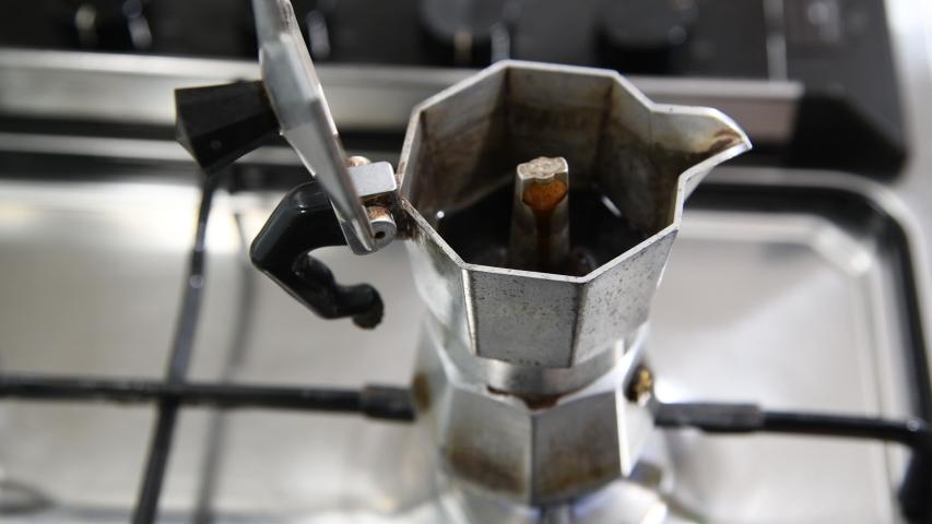 Moka pot on stove, Italain style coffee maker. Hot steam from Moka pot on portable gas stove.    Shutterstock HD Video #1049549755