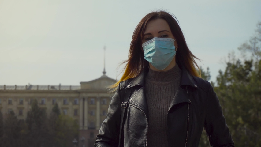 Woman tourist on surgical mask for corona virus prevention walking at city square with bag. Dangerous COVID-19 infection | Shutterstock HD Video #1049575135
