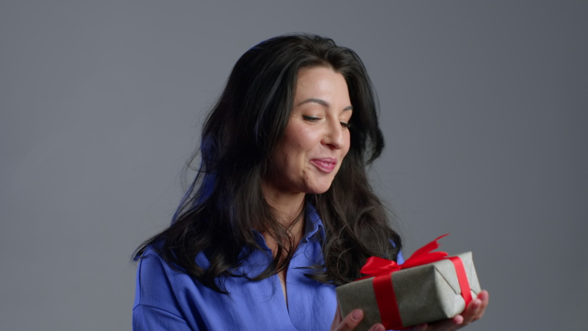 Excited adult woman received gift box with bow. She is happy and flattered by attention. Mature lady dancing with present on grey background. Studio footage. 4k. | Shutterstock HD Video #1049615755