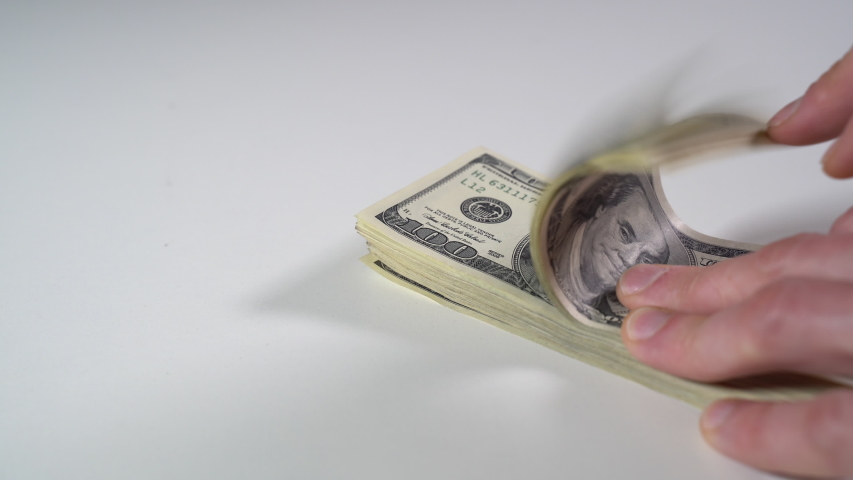 Check a pack of dollar bills on a white table. Close-up | Shutterstock HD Video #1049640835
