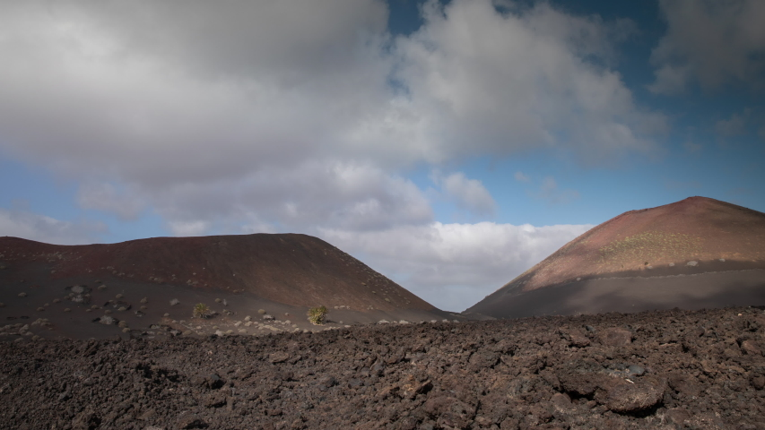 Timelapse of clouds passing over wild arid landscape of the Timanfaya National Park in Lanzarote. | Shutterstock HD Video #1049653345