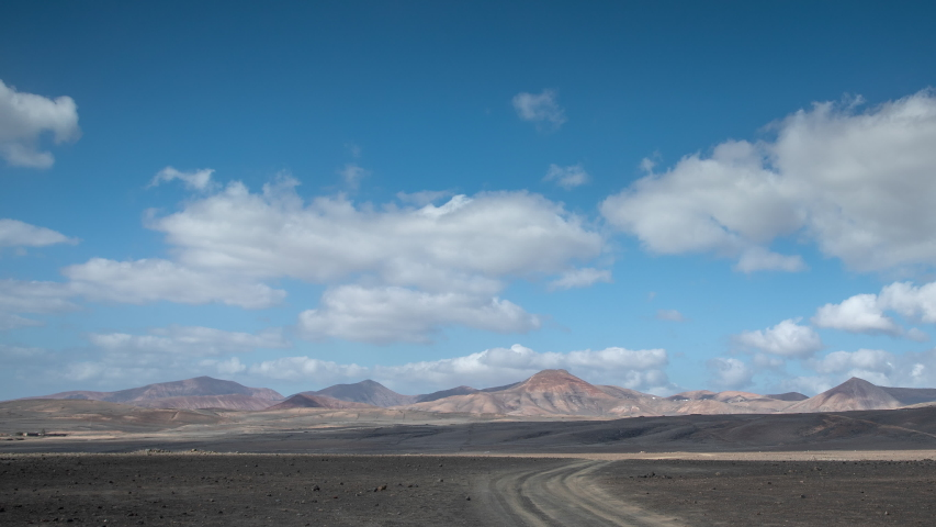 Timelapse of clouds passing over wild arid landscape of the Timanfaya National Park in Lanzarote. | Shutterstock HD Video #1049661295