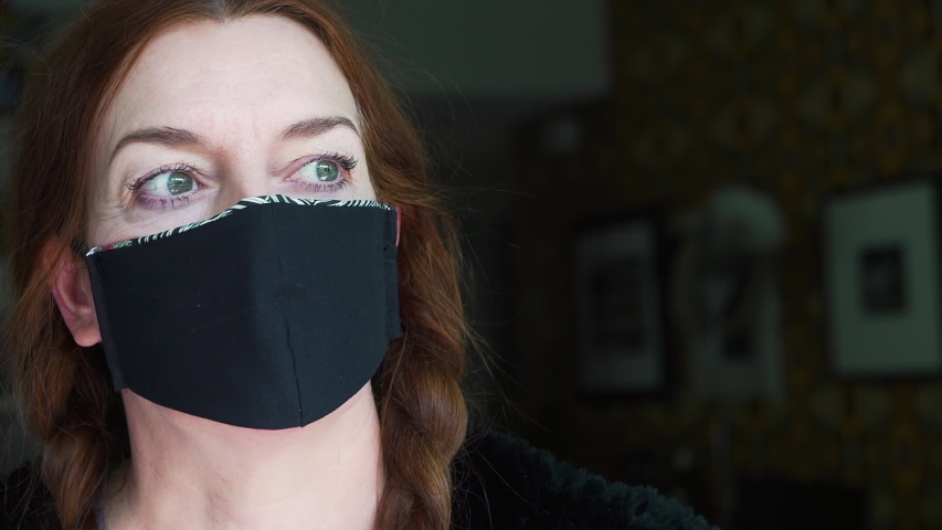 Portrait of an an experienced fashion designer wearing the face mask that she created at home  from recycled fabric as a protection against  viruses, disease and germs | Shutterstock HD Video #1049712415