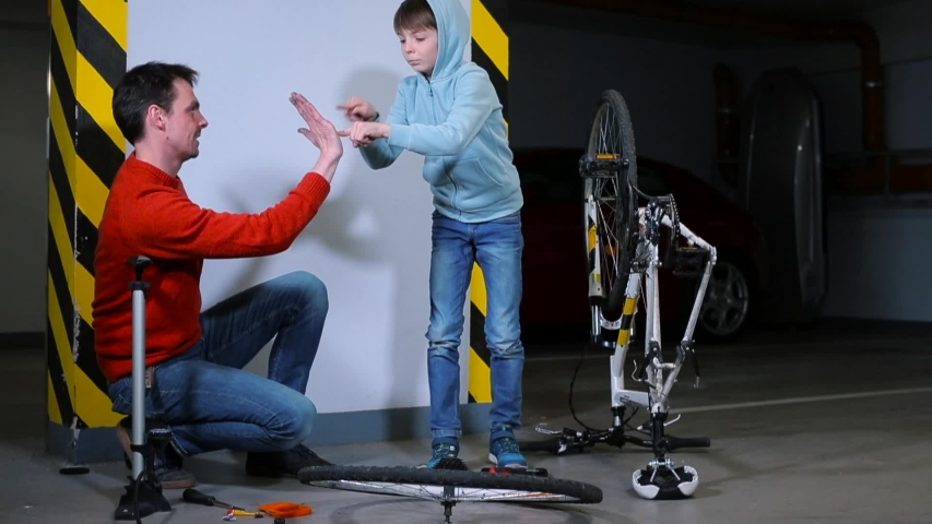 Father and son spend time in self-isolation. Bicycle wheel repair in the garage. Good mood in the family. Relaxation in self-isolation. | Shutterstock HD Video #1049780665