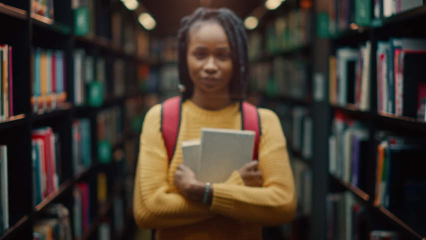 University Library Study: Portrait of a Smart Beautiful Black Girl Holding Study Text Books Smiling Looking at the Camera. Authentic Student Does Research for Class Assignment, Exams Preparationtion | Shutterstock HD Video #1049866975