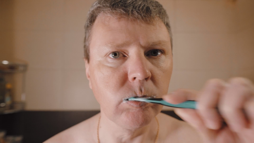 Funny white man writhes his face and brushes his teeth | Shutterstock HD Video #1049939095