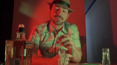 Caucasian man drinking tequila shots alone in bar. 4k