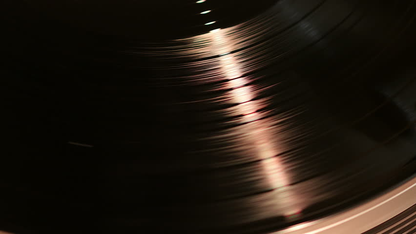 Close shot of vinyl spinning on a turntable with a streak of red light. | Shutterstock HD Video #10527725