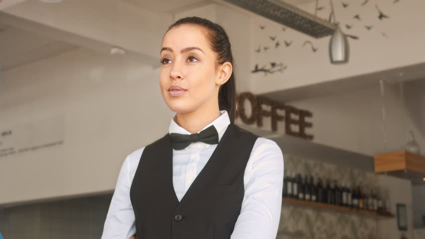 4k medium video of waiter/ hostess welcoming customer and showing them where they will be seated in restaurant.