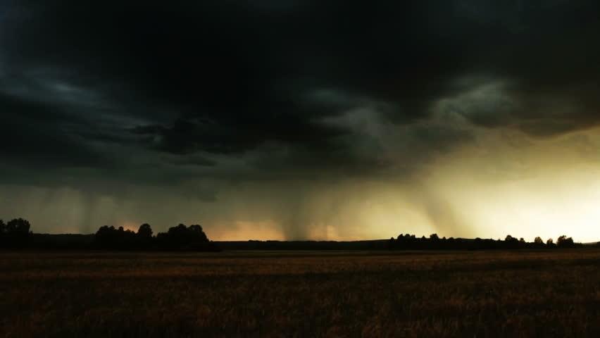 Evening thunder over a farm field. Lightning bolt strike.