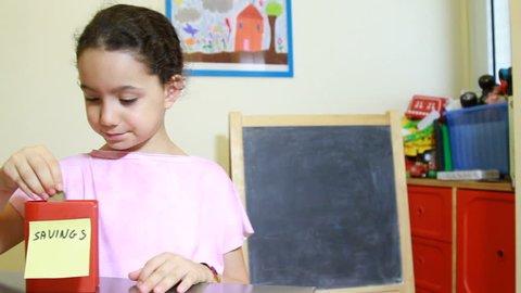 Kids saving money concept of girl insert coins to moneybox