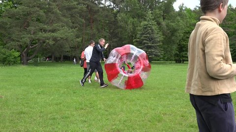 VILNIUS, LITHUANIA - MAY 23: Parent man push fast his boy son kid in red zorb ball bubble on park meadow on May 23, 2015 in Vilnius, Lithuania. Active recreation. Tracking follow panorama shot. 4K
