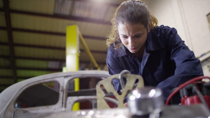 4K Attractive female mechanic working on car engine in garage workshop