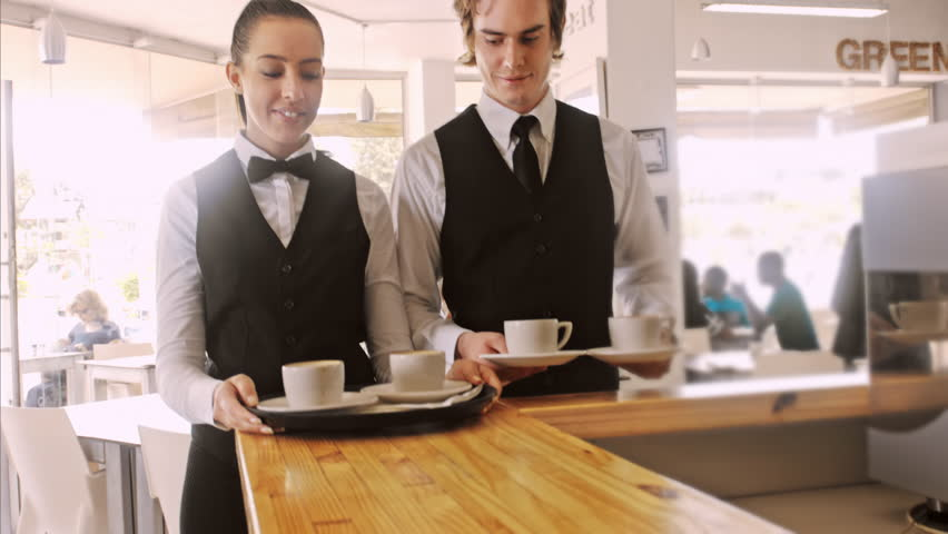 4k wide steadicam video of waiter and coffee on a tray, walking to a customer in hotel or restaurant cafe.