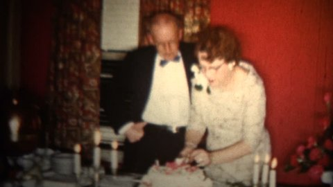 MINNEAPOLIS, MINNESOTA - OCTOBER 1958: An old couple celebrating their 50th wedding anniversary with a simple cake.