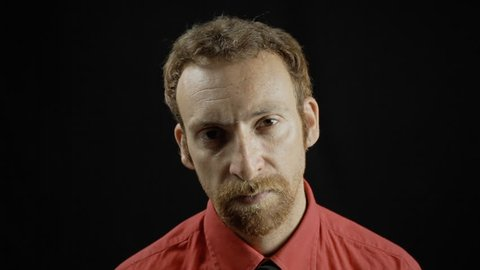 A hostile man's expression. Medium close-up shot of the face on black background. Part of a series of depictions of feelings and emotions with professional actors.