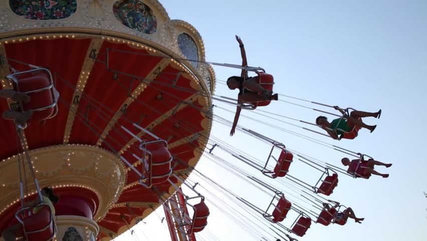 Many people ride on carousel. Under view with blue sky