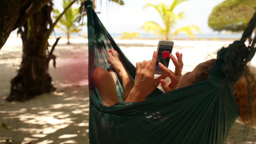 Woman holding smartphone Relaxing in a Hammock and getting animation heart  symbols. Collected Likes Concept - Relaxed Young Woman With Curly Hair Looking At Mobile Phone In